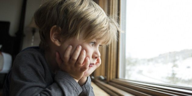 4 year old blonde boy looking out large window.