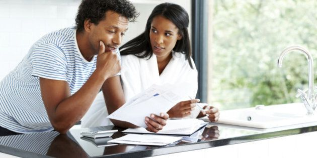 Portrait of worried young couple reading financial documents in kitchen
