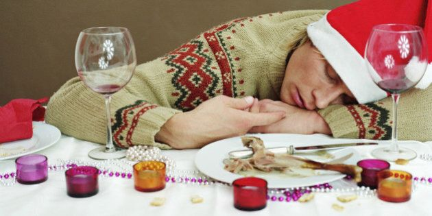 Young man in Santa hat sleeping at dinner table, resting head on