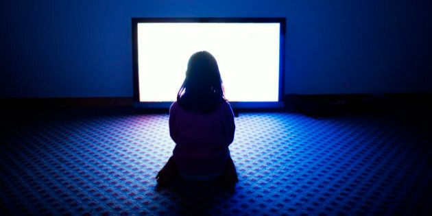 Girl sitting in front of flat screen television in dark