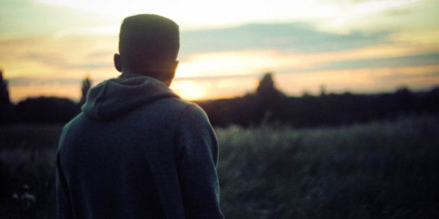 Young man staring into the distance watching the sun set