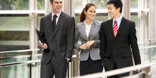 Three Business Colleagues Having Discussion Whilst Walking Outside