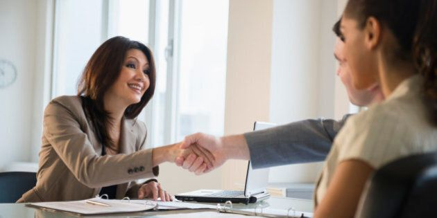 Businesswoman shaking hands with clients at