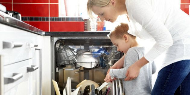 Young mother and her son loading a dishwasher in the