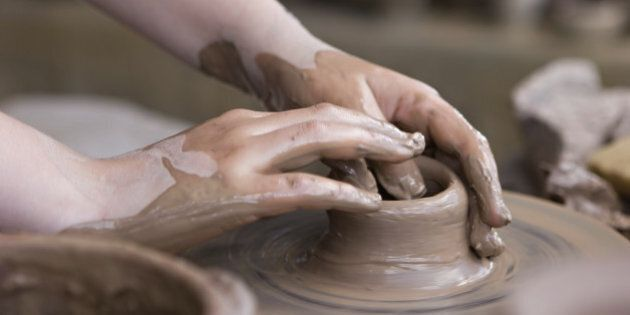 Hands closeup, working on pottery wheel with