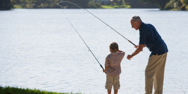 Man and young boy outdoors at park fishing in a