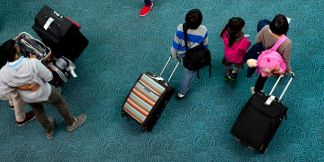 Travelers exit the arrivals gate at Vancouver International Airport (YVR) in Richmond, British Columbia,...