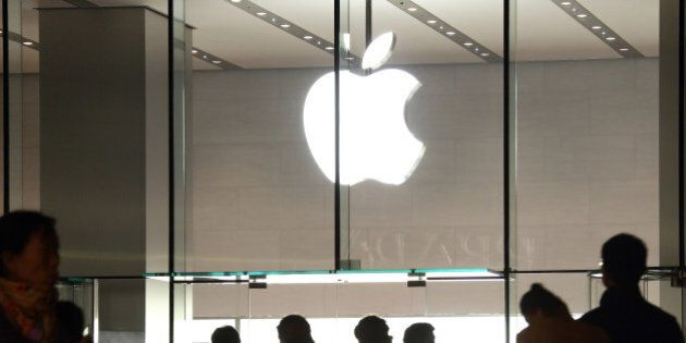 Pedestrians walk past the Apple Inc. store in the China Central Mall in Beijing, China, on Tuesday, Nov....