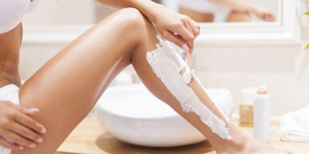 close up of woman shaving legs...