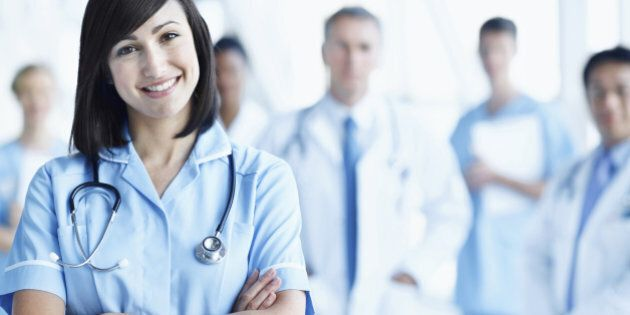 Portrait of a young nurse with her team in the