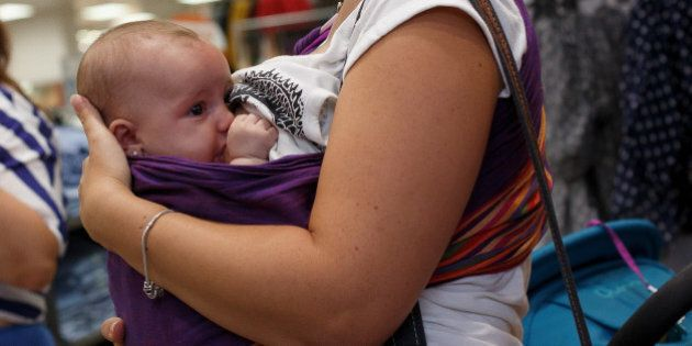 MADRID, SPAIN - AUGUST 23: A mother breast feeds her daughter during a protest at the entrance of a Primark...