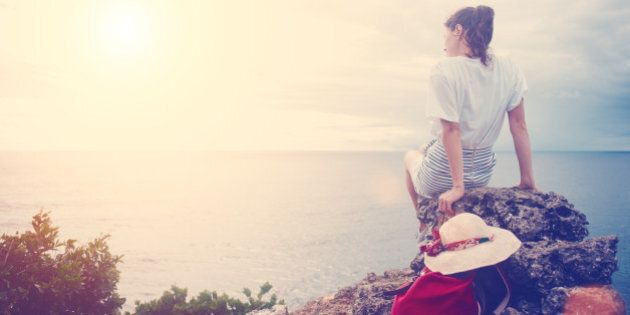 Young woman with hat and backpack sitting on a cliff and looking far away at the sea at sunset (intentional...