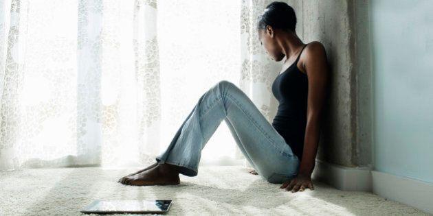 Young woman on floor next to ipad looking sad.