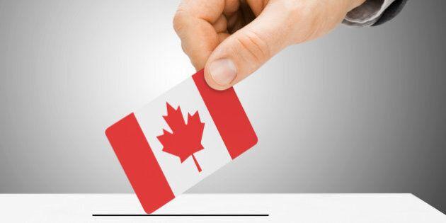 Voting concept - Male inserting flag into ballot box - Canada