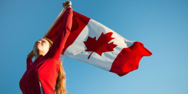 A young woman patriotically with long blond hair holds the Canadian flag above her head, as it blows...