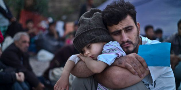 A Syrian refugee child sleeps on his father's arms while waiting at a resting point to board a bus, after...