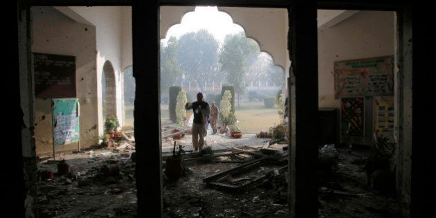 A Pakistan army soldier inspects the Army Public School attacked the day before by Taliban gunmen in...