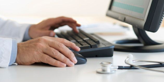 Male doctor's hands typing on desktop computer keyboard with