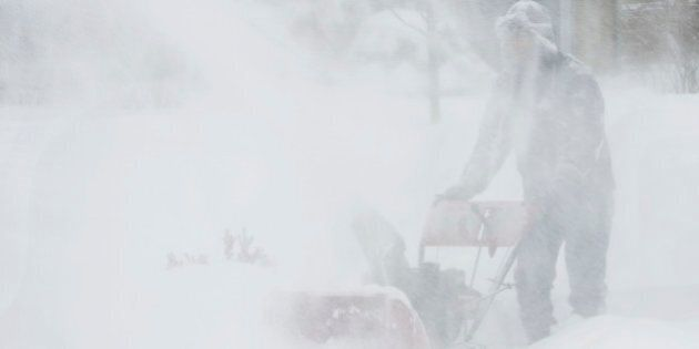 A man operating a snow blower while snow continues to fall; the resulting spray and the windblown snow...