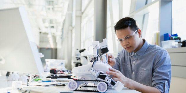 Focused engineer assembling robotic car