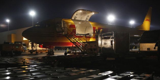 A cargo plane is unloaded on the tarmac during the overnight sort at the DHL Worldwide Express hub of...