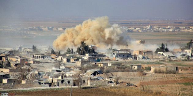 Smoke rises from buildings in the area of Tal Sharba following government air strikes on the outskirts of the northern Syrian city of Aleppo on December 27, 2015, as government forces seized the area from Islamic State (IS) group jihadists. AFP PHOTO / GEORGE OURFALIAN / AFP / GEORGE OURFALIAN        (Photo credit should read GEORGE OURFALIAN/AFP/Getty Images)