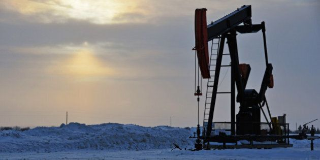An oil well pump jack in a snow covered winter landscape.