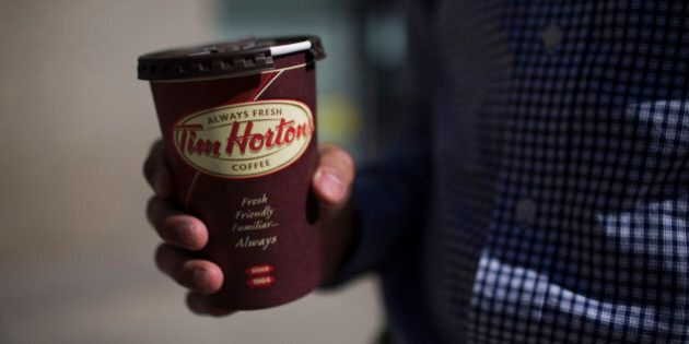 A customer holds a coffee cup outside a Tim Hortons Inc. restaurant in Toronto, Ontario, Canada, on Monday,...