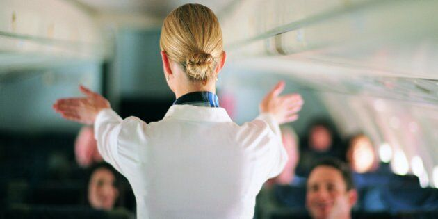 Rear View of Air Stewardess Explaining Aeroplane Safety to