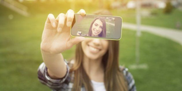 Beautiful young woman photographing herself with phone. Cute smiling young Caucasian teenage girl taking...
