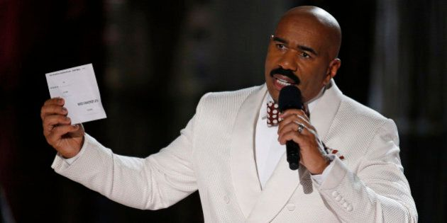 Steve Harvey holds up the card showing the winners after he incorrectly announced Miss Colombia Ariadna...