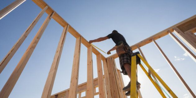 Caucasian man measuring frame on construction