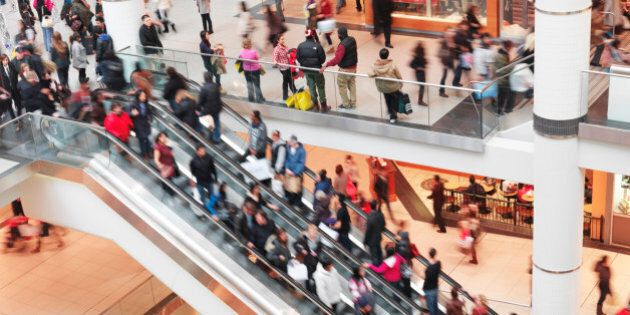 Blurred with motion people on an escalator at Toronto Eaton Centre shopping mall on Boxing day 2011....