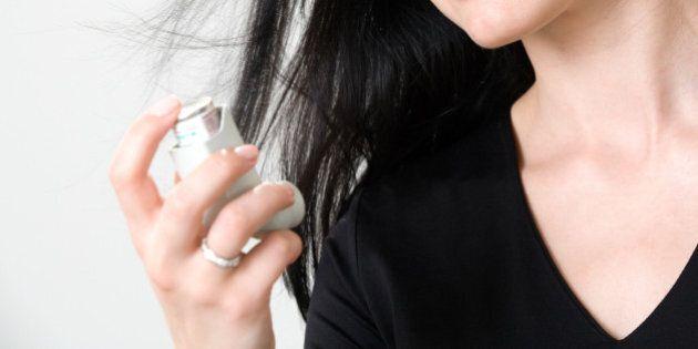 Studio shot of woman holding inhaler