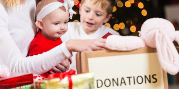 Mom with children choosing toys to donate to Christmas charity