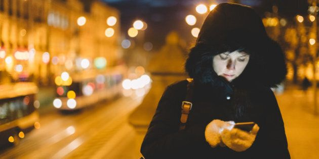 Woman in winter clothing texting in an urban