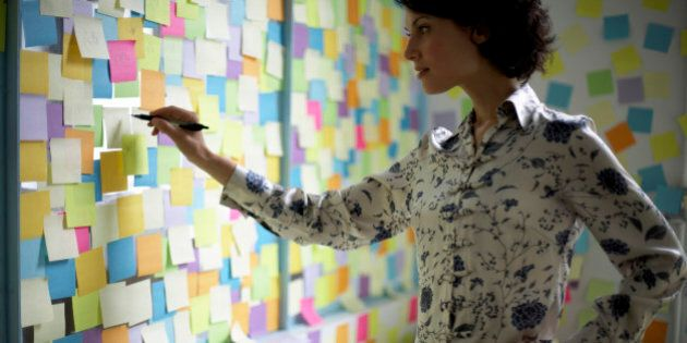 Woman writing on wall covered with adhesive notes
