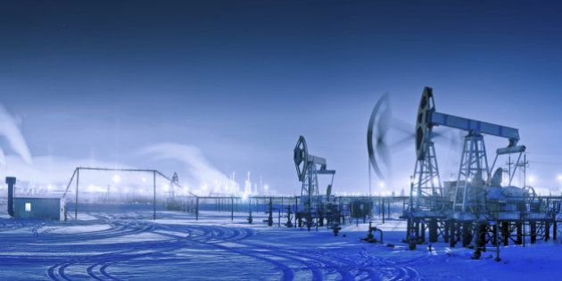 Oil and gas industry. Panoramic of a pumpjack and oil refinery in the winter with snow. Night