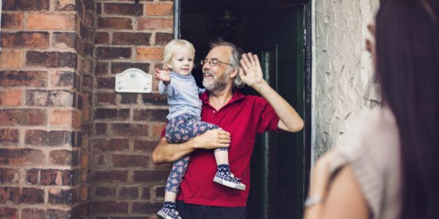 Happy smiling little toddler girl with her Grandpa waving goodbye to her Mummy who is leaving to go to work