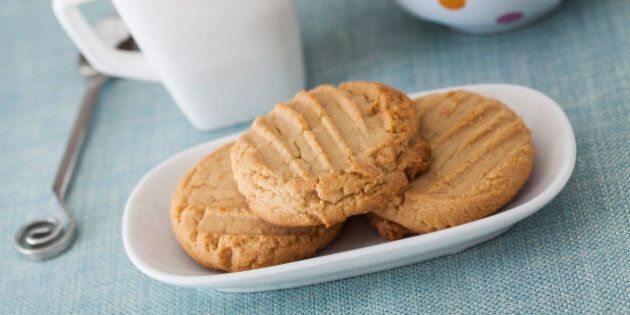 High Key image of 3 peanut butter cookies on a white oblong plate with a blue cloth along with a cup of tea and a polka dot teapot in the background.