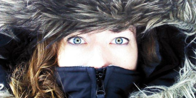 Close up of woman's face, focused on green eyes, zipped inside the hood of a large winter coat or parka,...