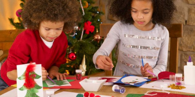 Mixed race children making Christmas cards with glitter and feathers on dining room table