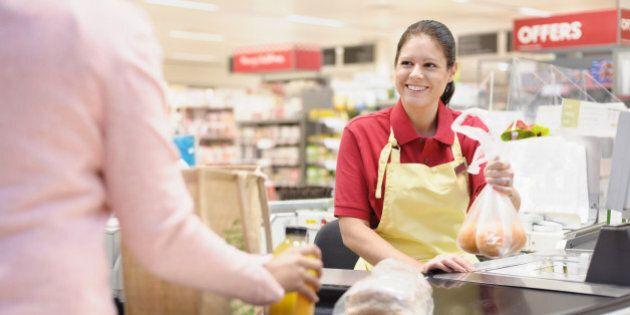 Hispanic woman helping customer at grocery