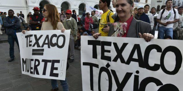 Activists holds signs reading 'Texaco = Death' and 'Texaco = Toxic' as they protest against US multinational...