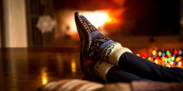 Closeup portrait of feet at woolen socks warming at fireplace in