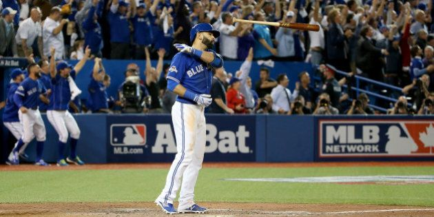 TORONTO, ON - OCTOBER 14: Jose Bautista #19 of the Toronto Blue Jays flips his bat up in the air after...