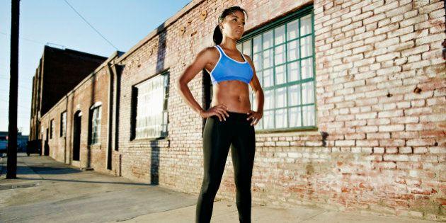 Black runner standing on city