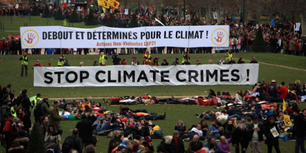 Activists gather during a demonstration near the Eiffel Tower, in Paris, Saturday, Dec.12, 2015 during the COP21, the United Nations Climate Change Conference. As organizers of the Paris climate talks presented what they hope is a final draft of the accord, protesters from environmental and human rights groups gather to call attention to populations threatened by rising seas and increasing droughts and floods. Banner behind reads: Standing and decided for climate. (AP Photo/Thibault Camus)