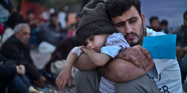 FILE - In this Sunday, Oct. 4, 2015 file photo, a Syrian refugee child sleeps in his father's arms while...