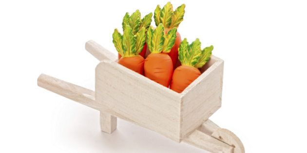Delicious orange toy carrot in a wooden cart isolated on